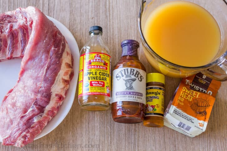 Ingredients for instant pot ribs with ribs, apple juice, vinegar, bbq sauce, seasoning salt and rib rub