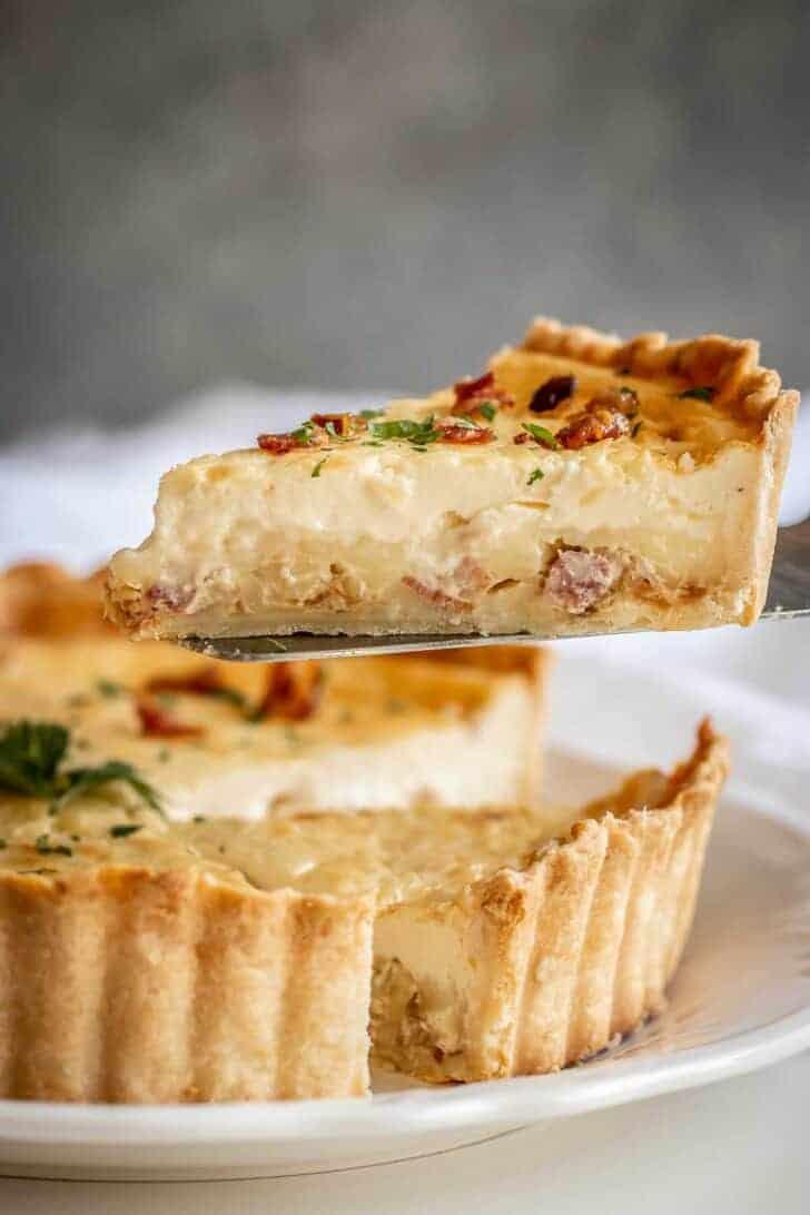 A slice of classic quiche Lorraine slice raised above the tart.
