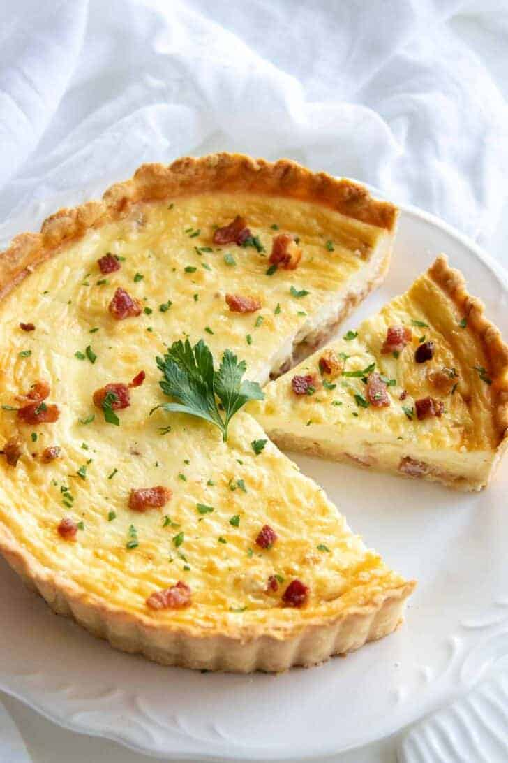 Quiche Lorraine recipe on a serving platter, sliced for serving
