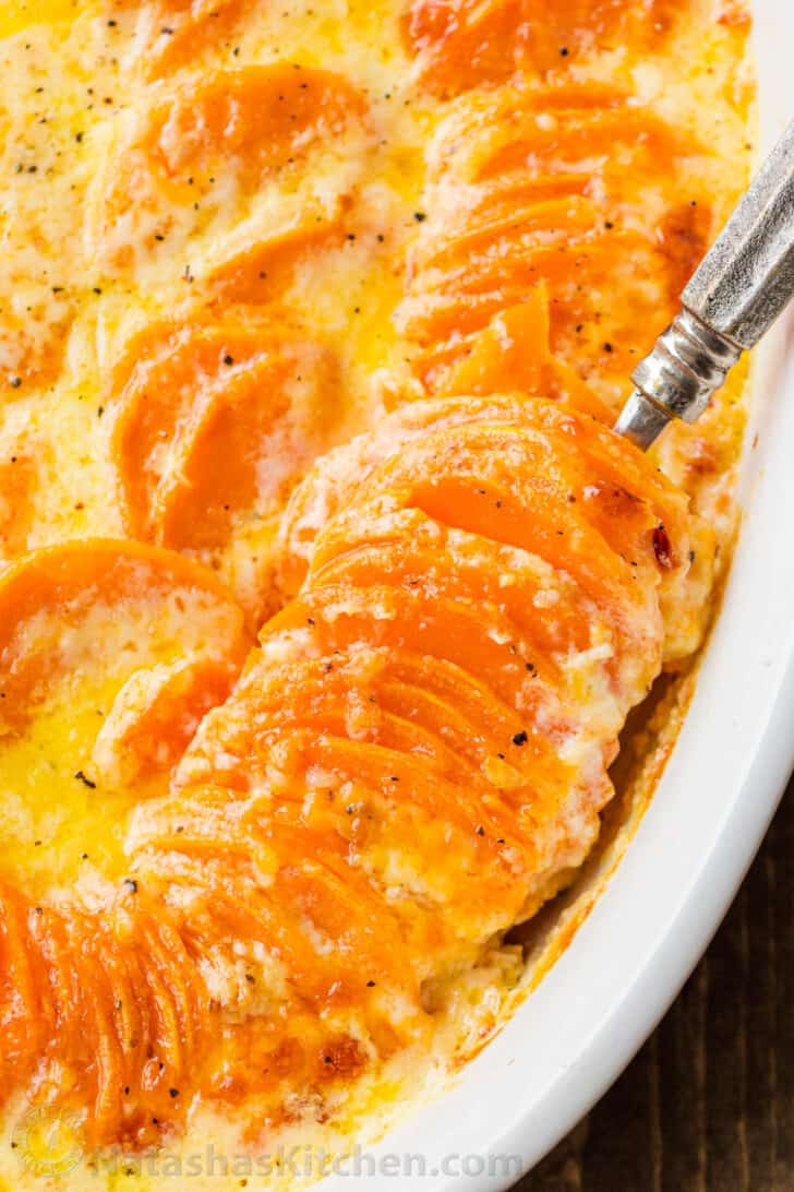 Stacked scalloped potatoes in a dish with a creamy sauce.