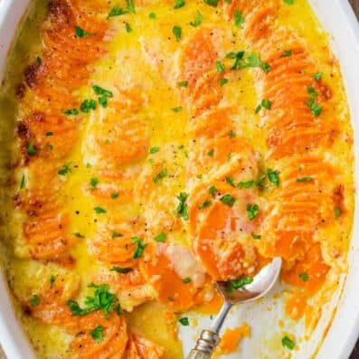 Scalloped Sweet Potatoes in casserole dish with serving spoon