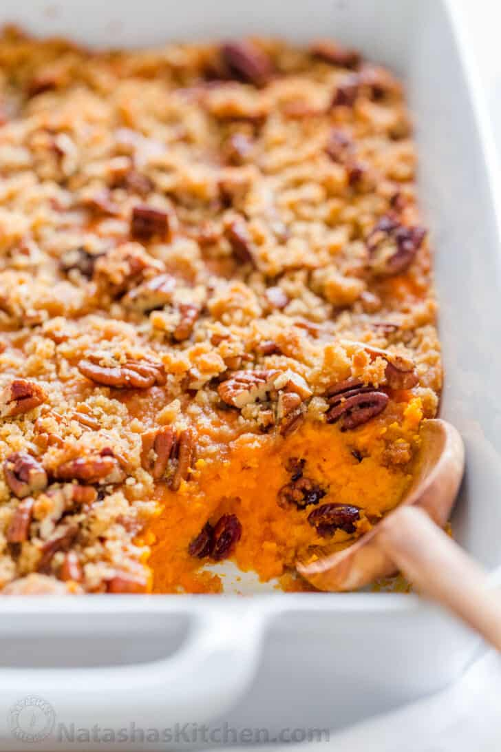 Sweet potato casserole recipe with pecan topping with serving spoon
