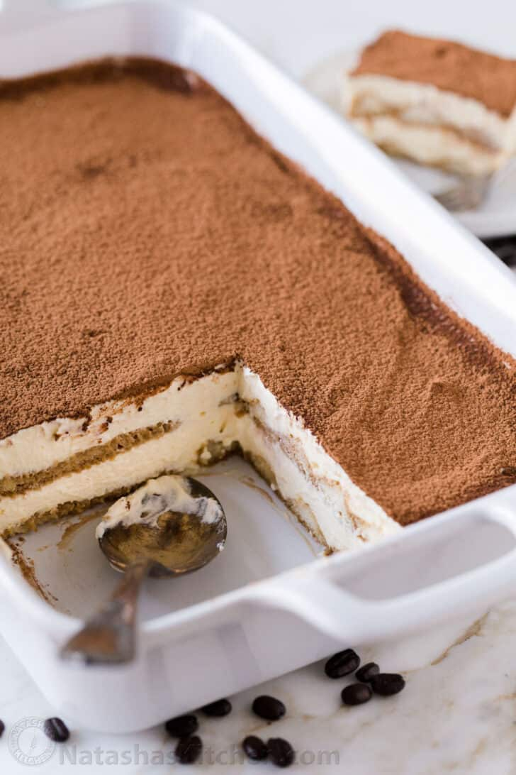 Tiramisu dessert served in a casserole dish with serving spoon