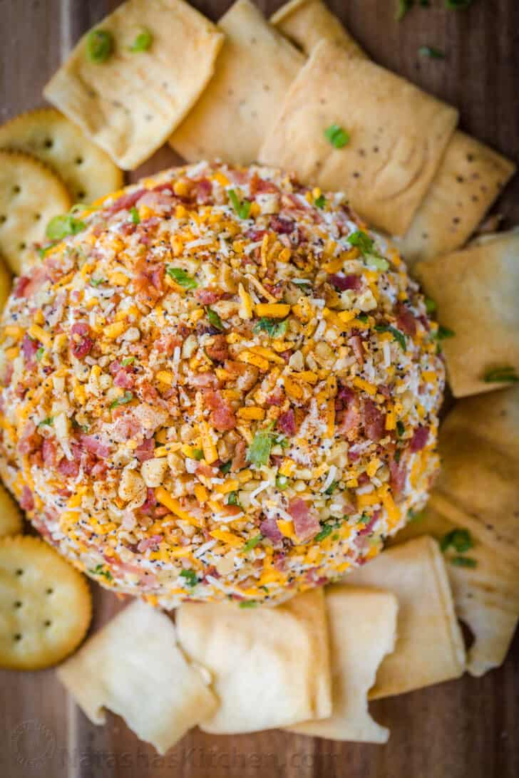 Cheese ball surrounded with crackers and pita chips.