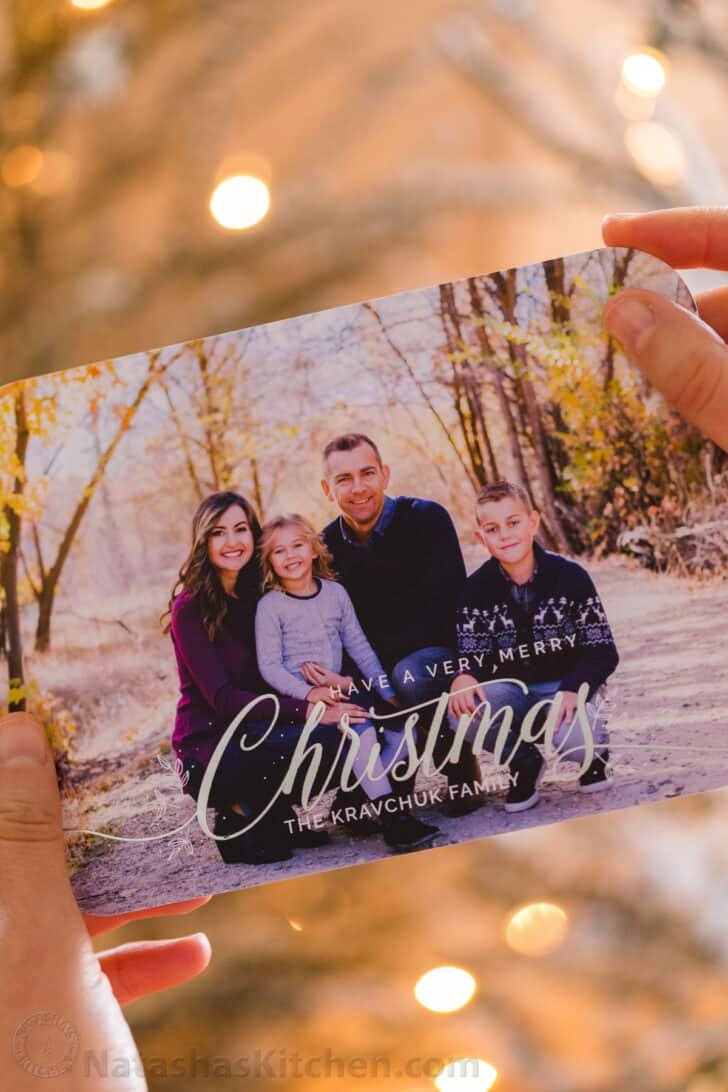 Someone holding a Christmas card that has a photo of a family.