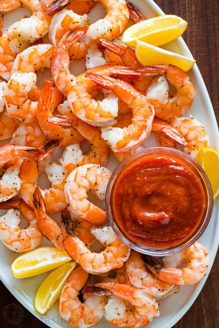 Perfectly baked shrimp on serving platter with shrimp cocktail sauce