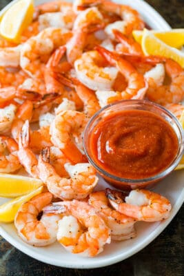 Shrimp cocktail with baked shrimp and homemade shrimp cocktail sauce on platter with lemon wedges