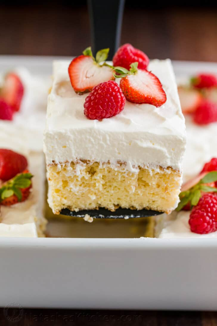 Moist slice of tres leches cake on a spatula with casserole beneath
