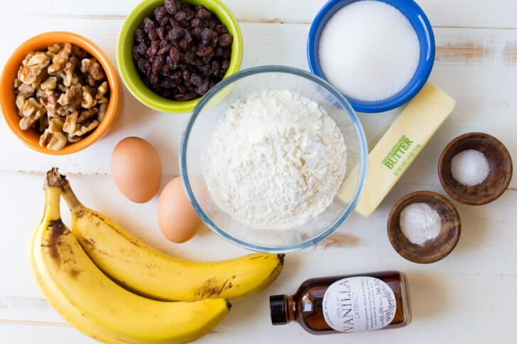 Ingredients for Banana Bread with ripe bananas, flour, sugar, eggs, butter, walnuts and raisins