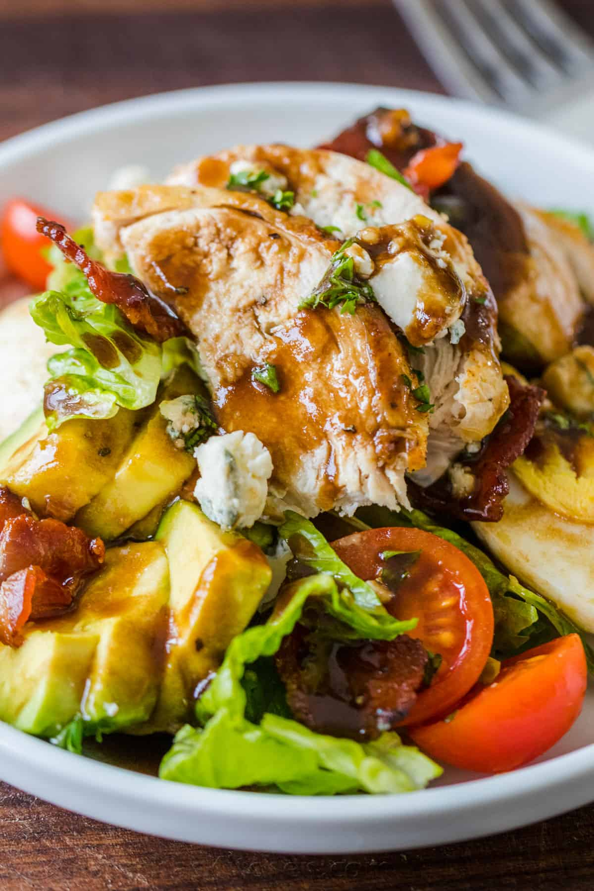 Cobb salad served on a plate with chicken and cobb salad dressing drizzled over the top