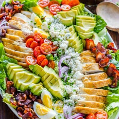 Chicken Cobb Salad on a platter with salad dressing in a mason jar