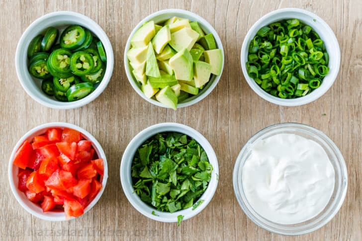 Nacho toppings in ramekins with tomatoes, avocados, chives, cilantro, jalapeños and sour cream