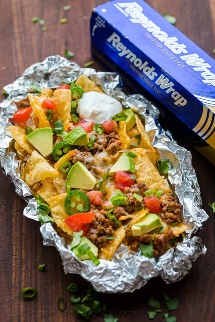 Foil pack nachos with avocado and tomato toppings on top