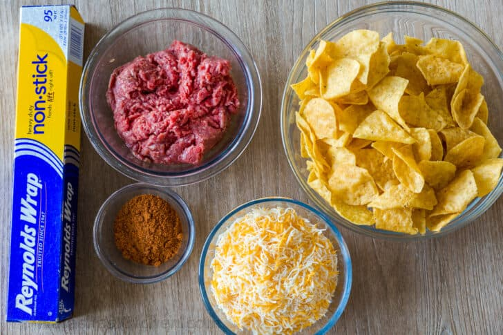 Ingredients for foil pack nachos with aluminum foil, ground beef, taco seasoning, Mexican cheese and tortilla chips