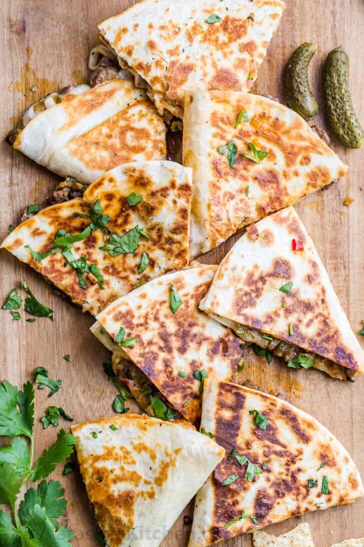 Philly Cheesesteak Quesadillas cut into triangles on cutting board