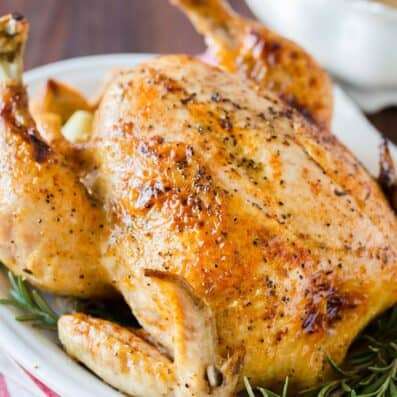 Whole chicken cooked in the instant pot served on a platter with gravy