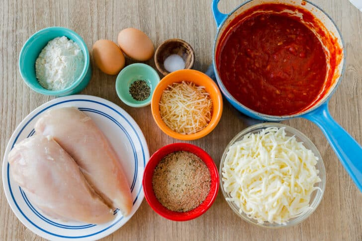 Ingredients for chicken parmesan with homemade marinara sauce, chicken breast, cheese, bread crumbs, eggs, flour and seasonings
