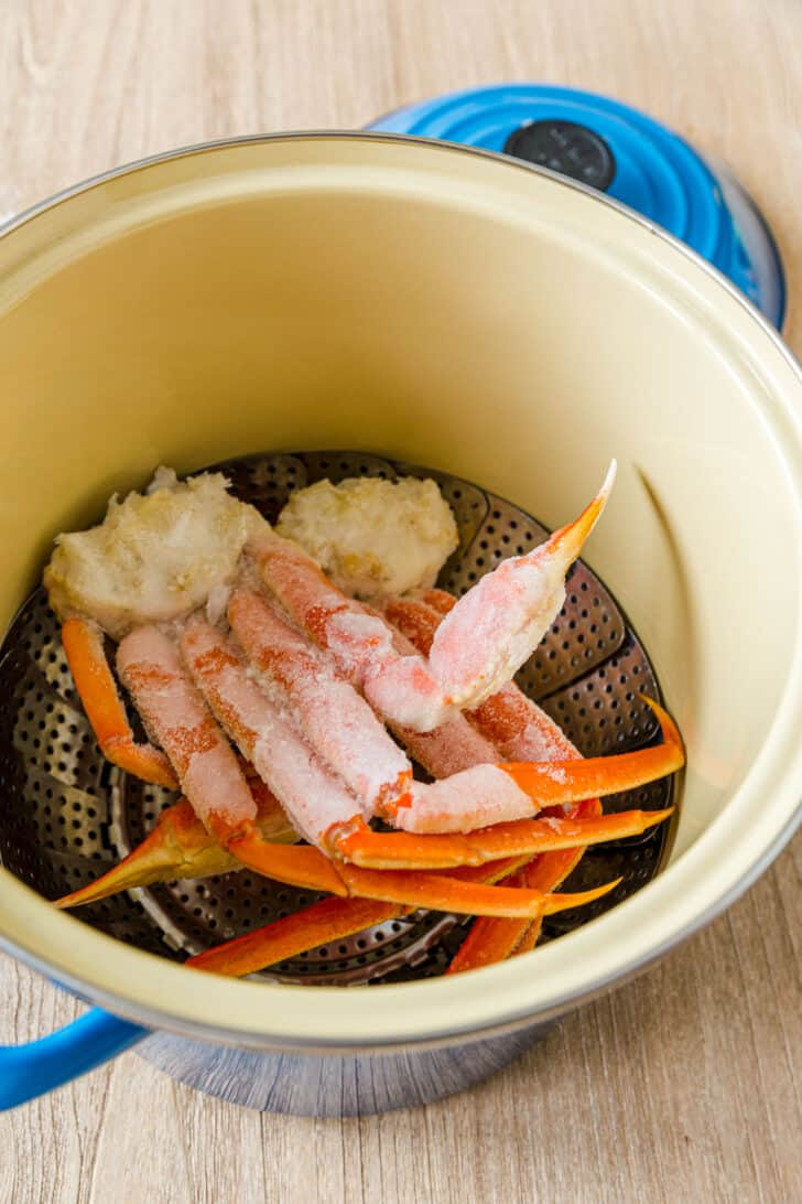 Crab legs in pot with steaming basket