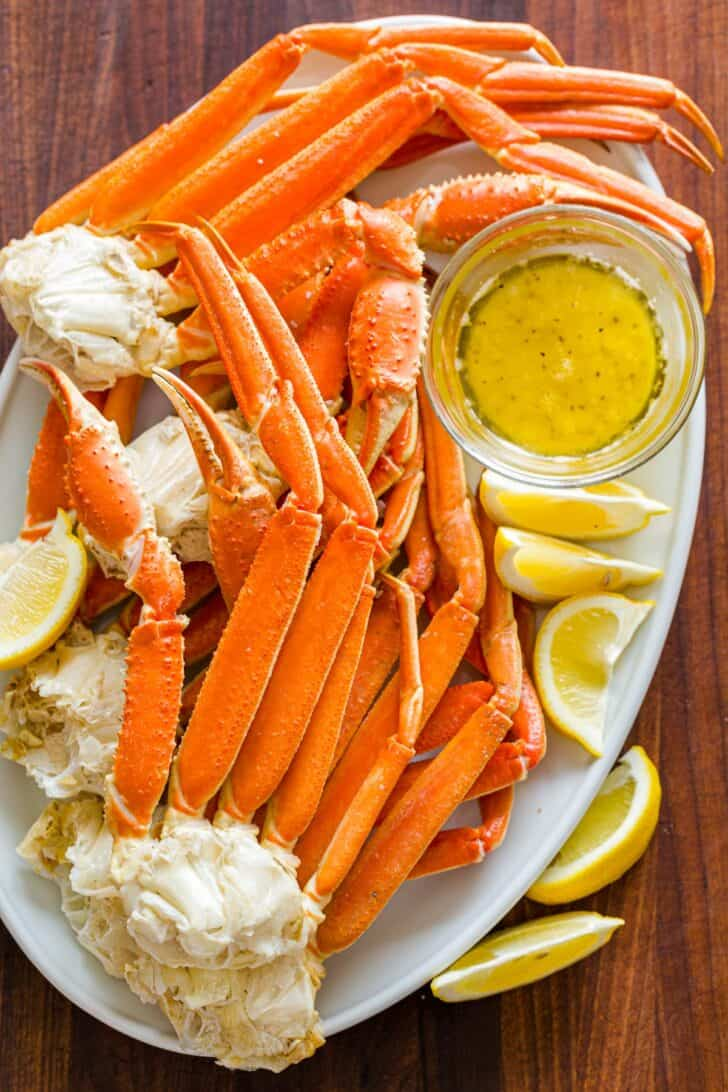 Cooked Crab legs on a serving platter with butter dipping sauce and lemon wedges