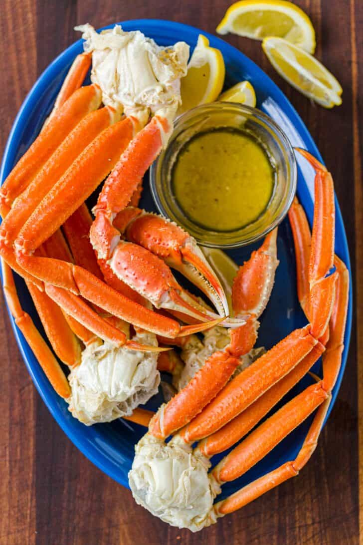 Cooked crab legs on blue platter served with dipping sauce