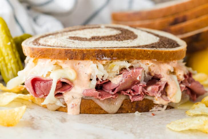 Classic Reuben on a plate with pickles and chips.
