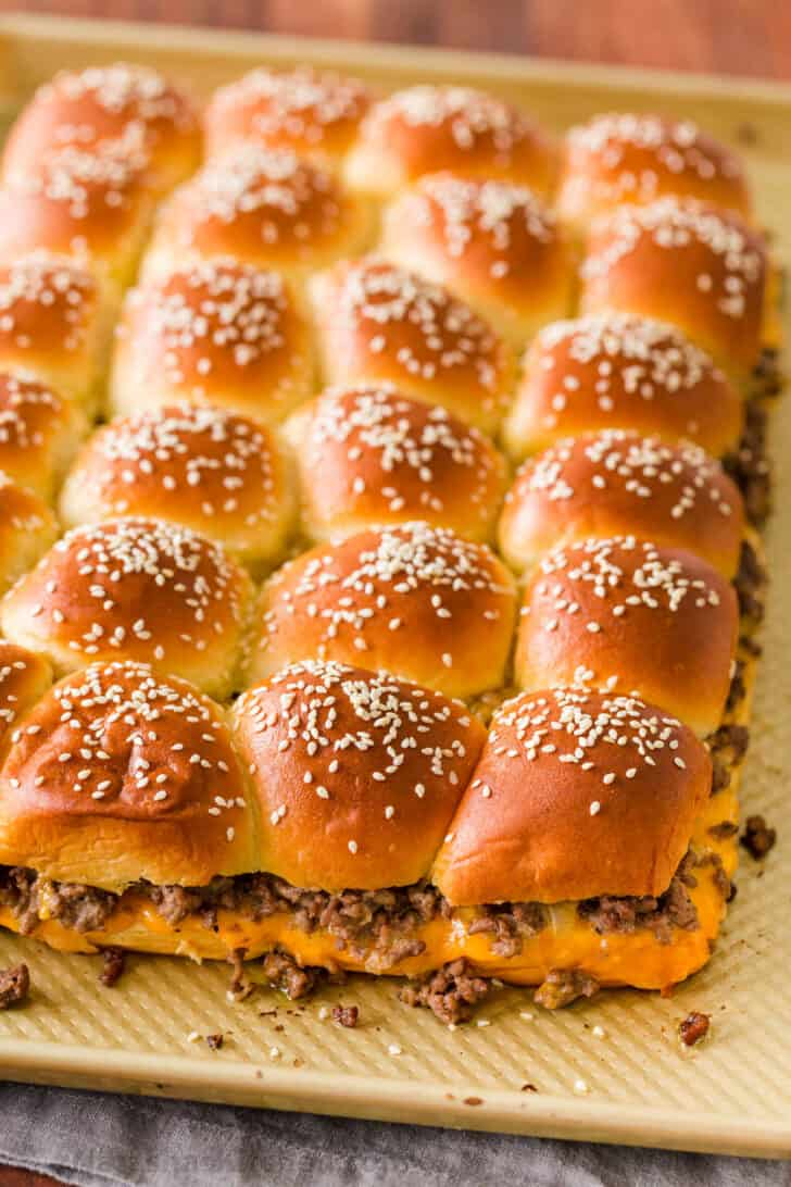 Cheeseburger sliders on a baking sheet topped with sesame seeds