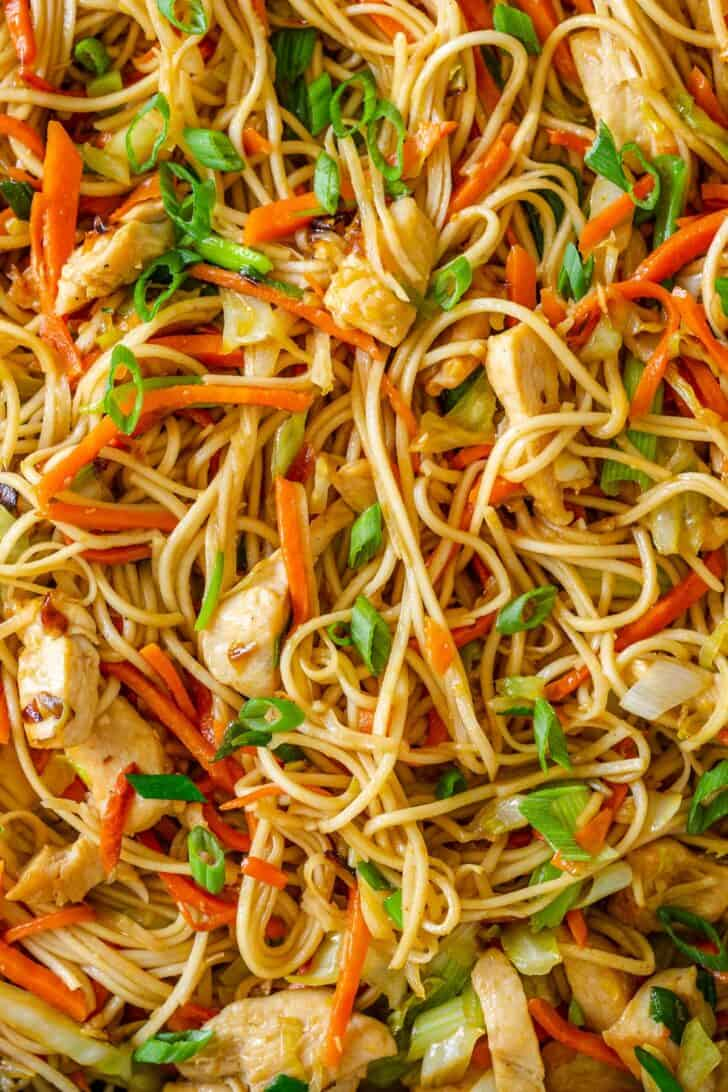 Chow mein with chicken and vegetables close up in pan