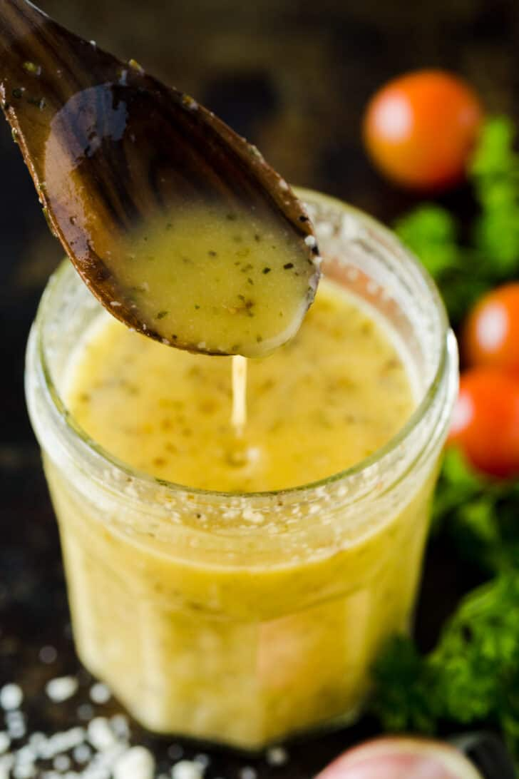 Homemade Italian dressing in a mason jar pouring form a spoon