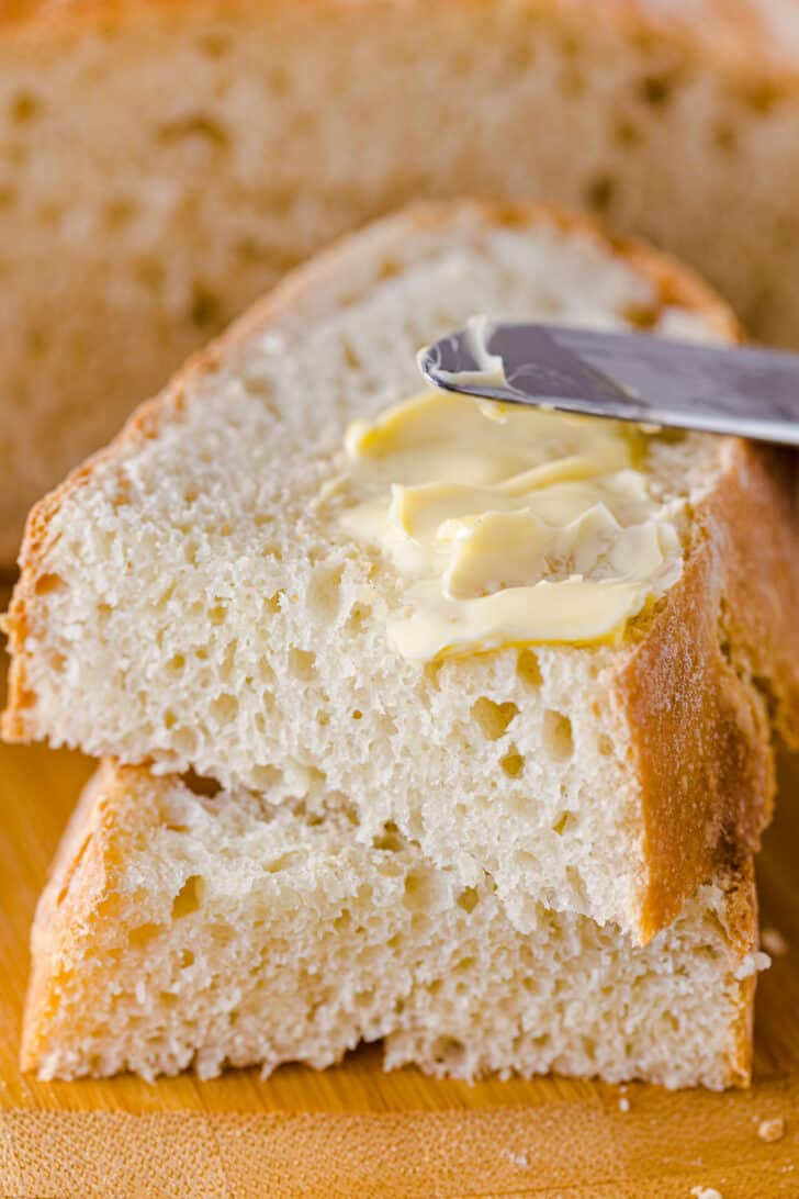 2 slices of artisan bread with butter spread with a knife