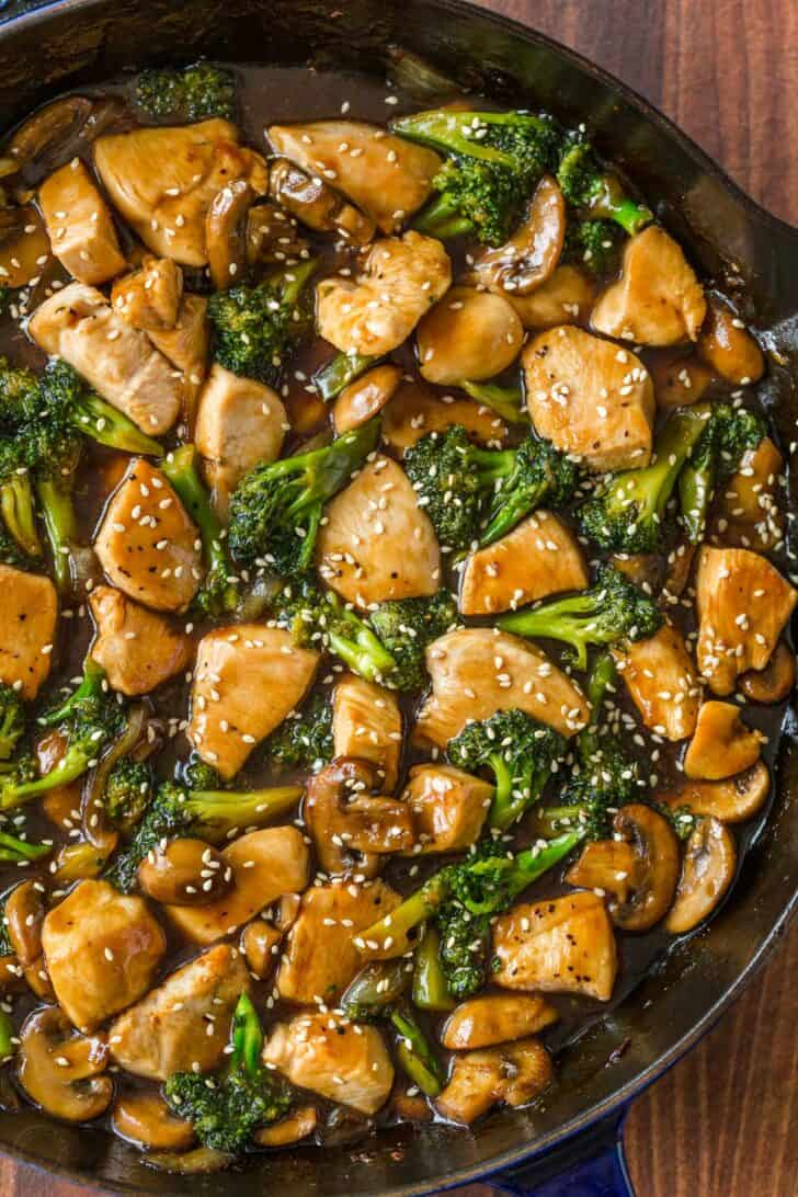 Chicken and broccoli and mushroom stir fry with sauce in skillet