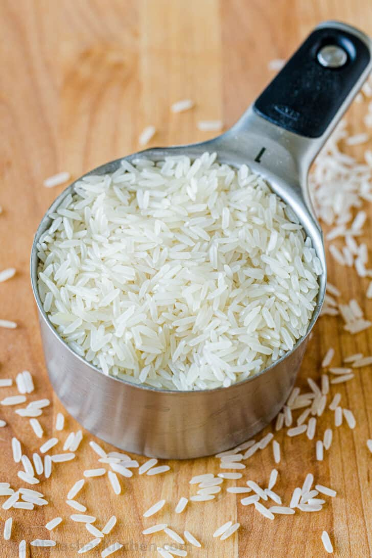 Jasmine white long grain rice in a measuring cup with rice surrounding the base