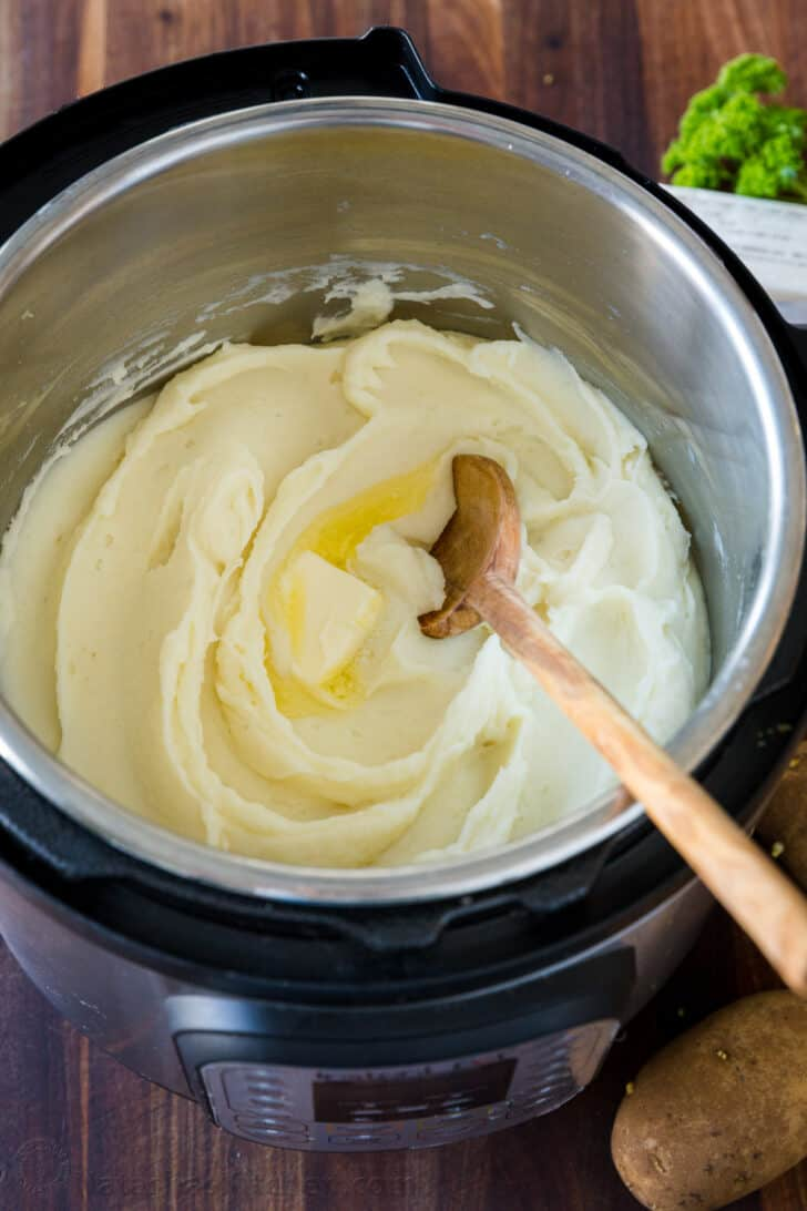Creamy mashed potatoes inside the bowl of an insta pot topped with butter