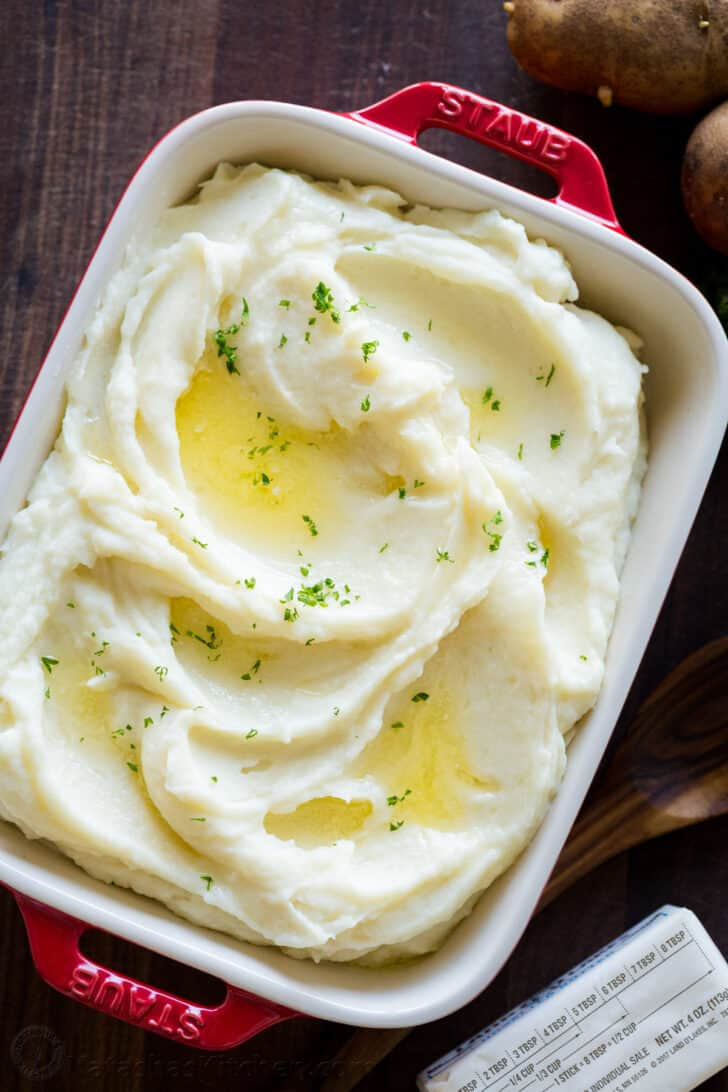 Creamy mashed potatoes in a casserole dish surrounded by russet potatoes and butter