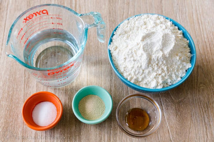 Pizza dough ingredients with warm water, flour, yeast, salt and honey