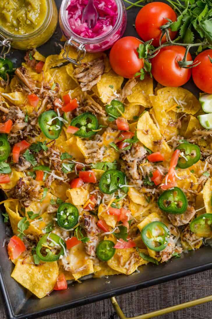 A tray of nachos with vibrant veggies on top