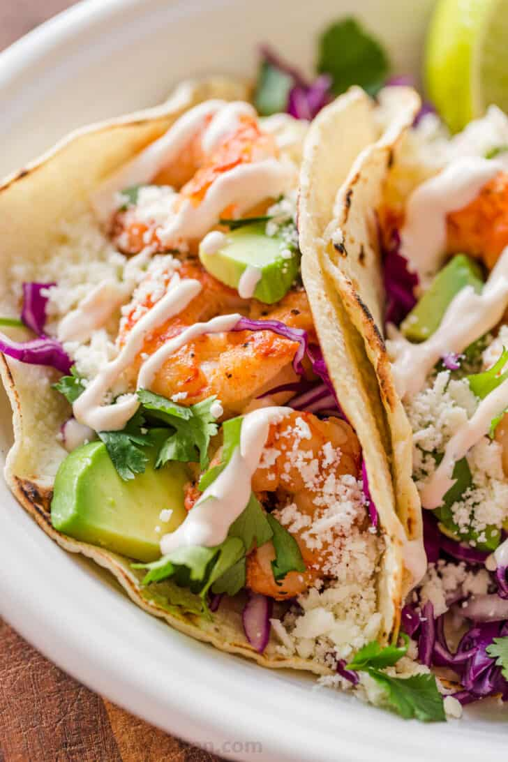 Side profile of tacos laying on platter loaded with shrimp and drizzled with sauce