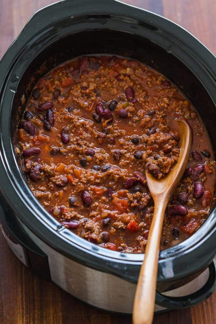 Chili in a slow cooker with spoon