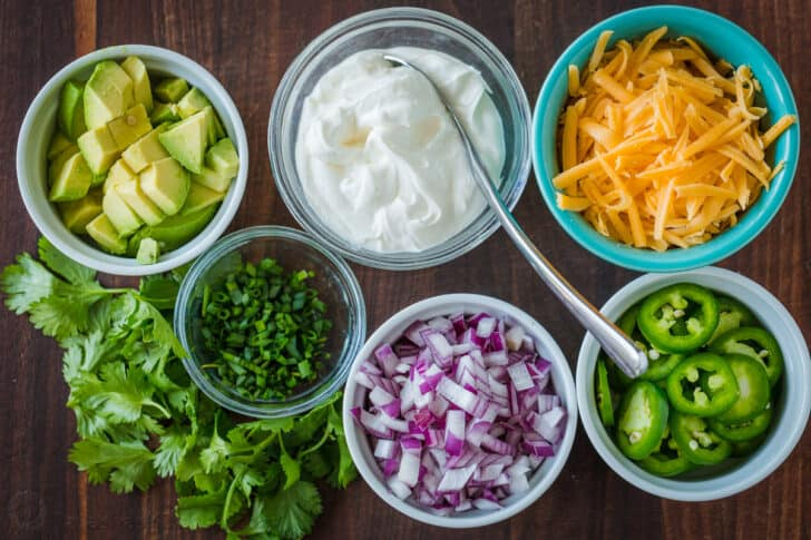 Toppings for chili with avocados, chives, onion, jalapeños, cheese, sour cream and cilantro