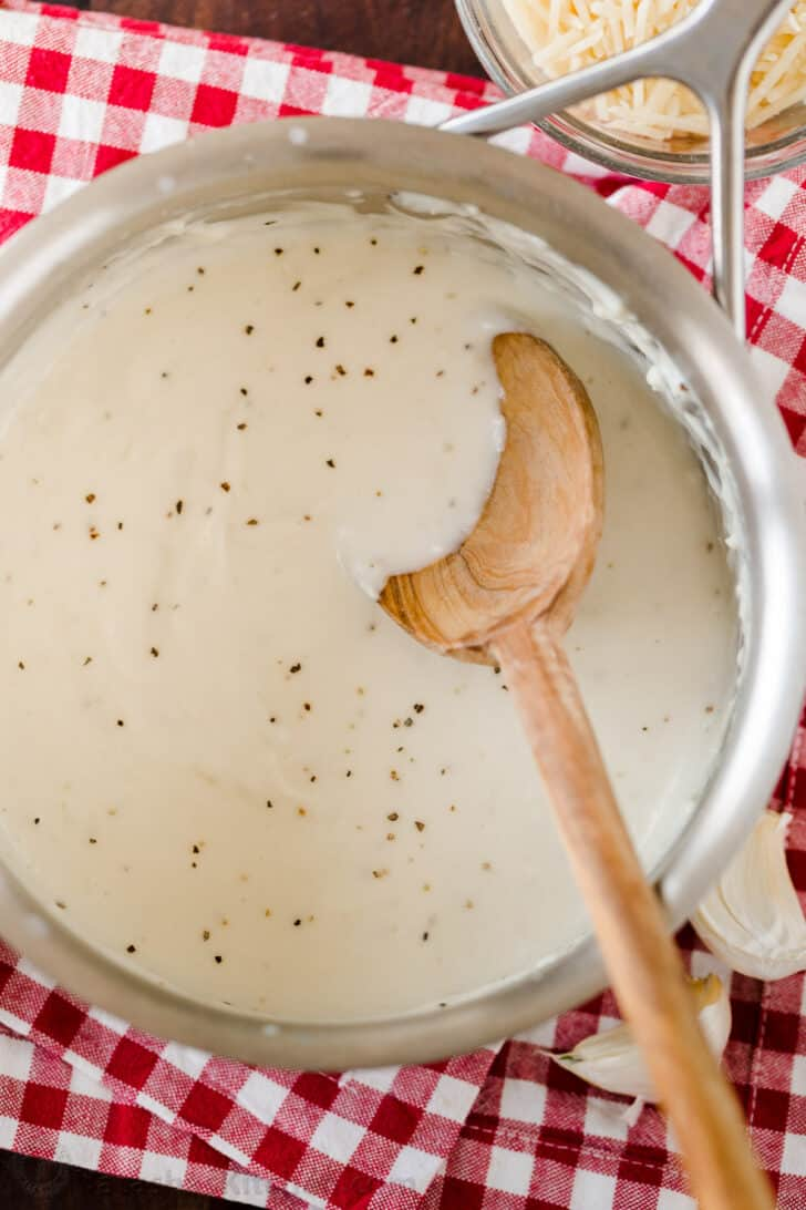 white garlic pizza sauce in a saucepan with mixing spoon