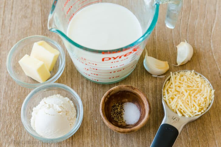 Ingredients for white pizza sauce with milk, parmesan, garlic, butter, flour and seasonings