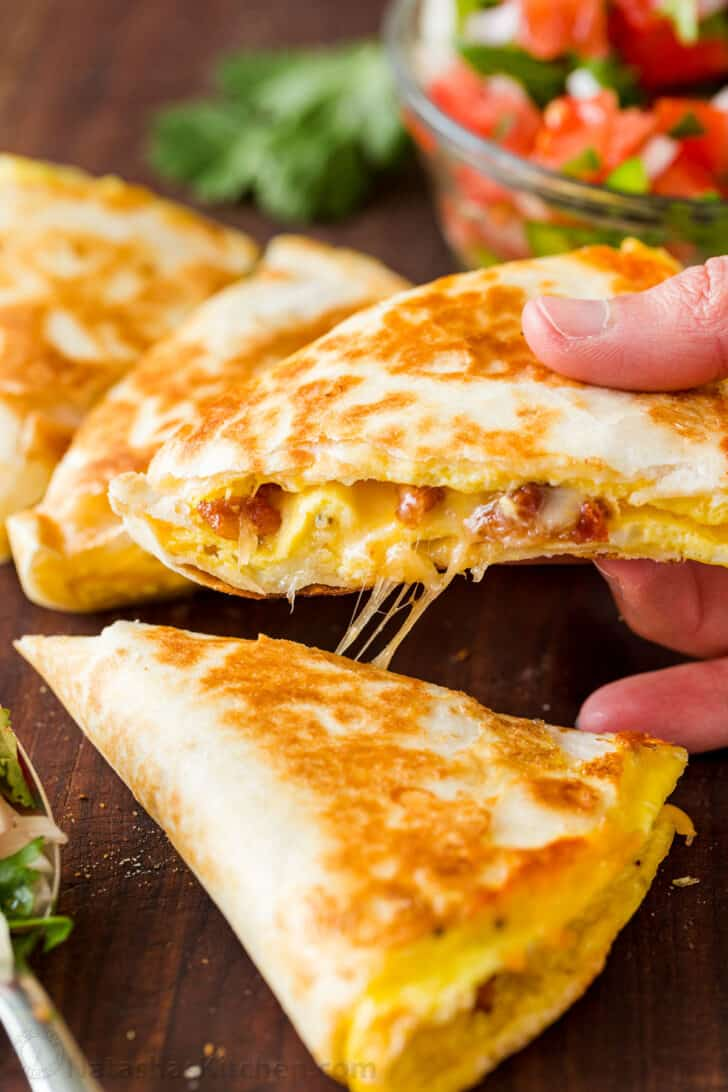 Breakfast quesadilla cut into wedges and lifted with cheese pull