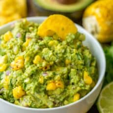 Grilled corn guacamole in a bowl with a tortilla chip