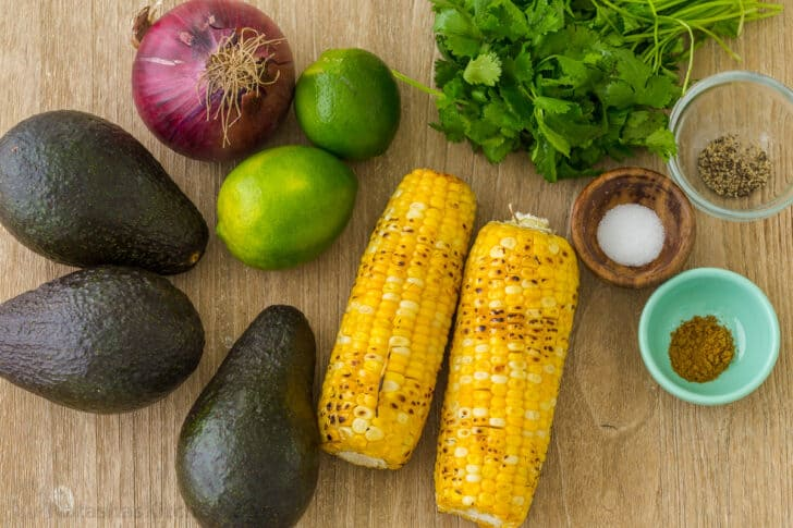 Ingredients for corn guacamole with avocados, corn, cilantro, red onion, limes and seasonings