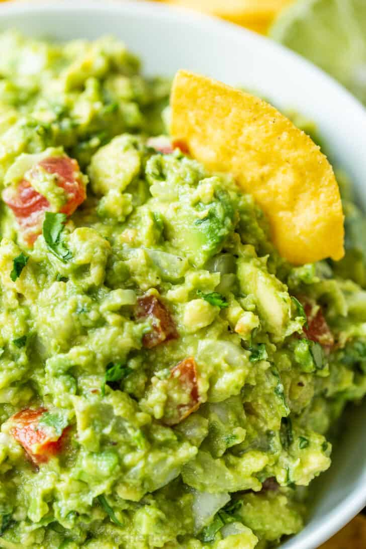 Ripe avocados mashed and combined with guacamole ingredients with tortilla chip