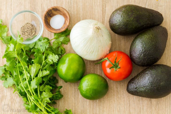 Ingredients for guacamole with avocados, tomato, onion, cilantro, lime, salt and pepper