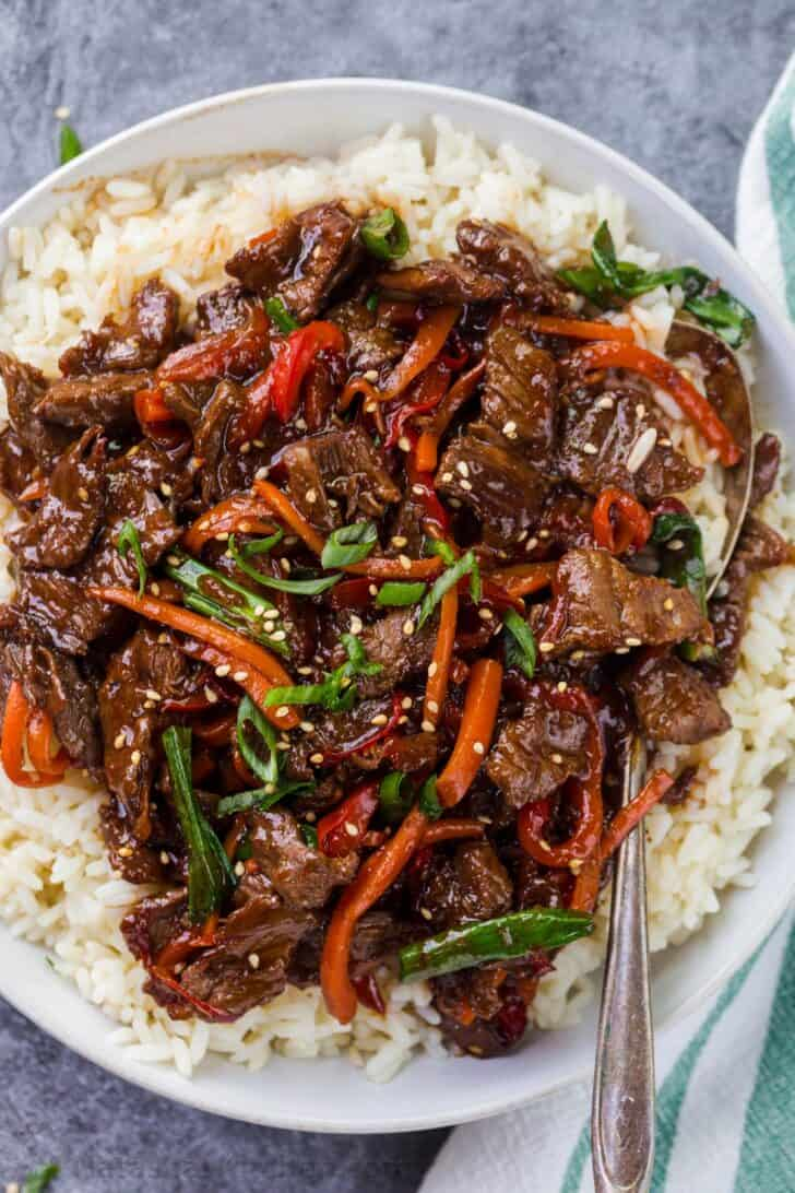 Beef and vegetables over a bed of rice with a spoon and a napkin.