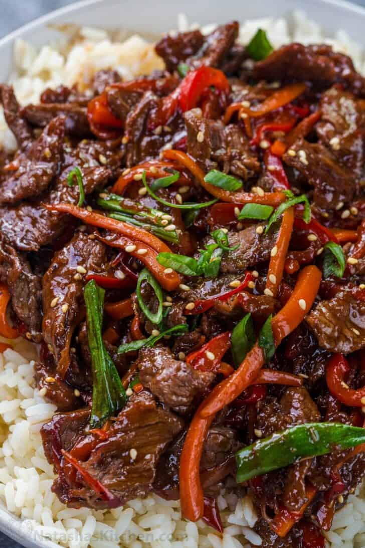 Slices of beef with vegetables in a sauce over tice in a plate topped with green onion and sesame seed.