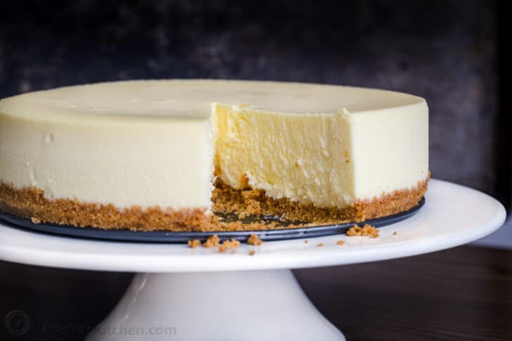 Classic Cheesecake on cake platter with slice removed