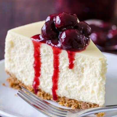 Slice of cheesecake on a plate topped with cherry sauce