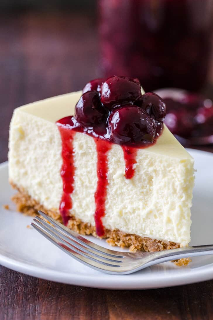 Classic slice of cheesecake on a plate with cherry topping